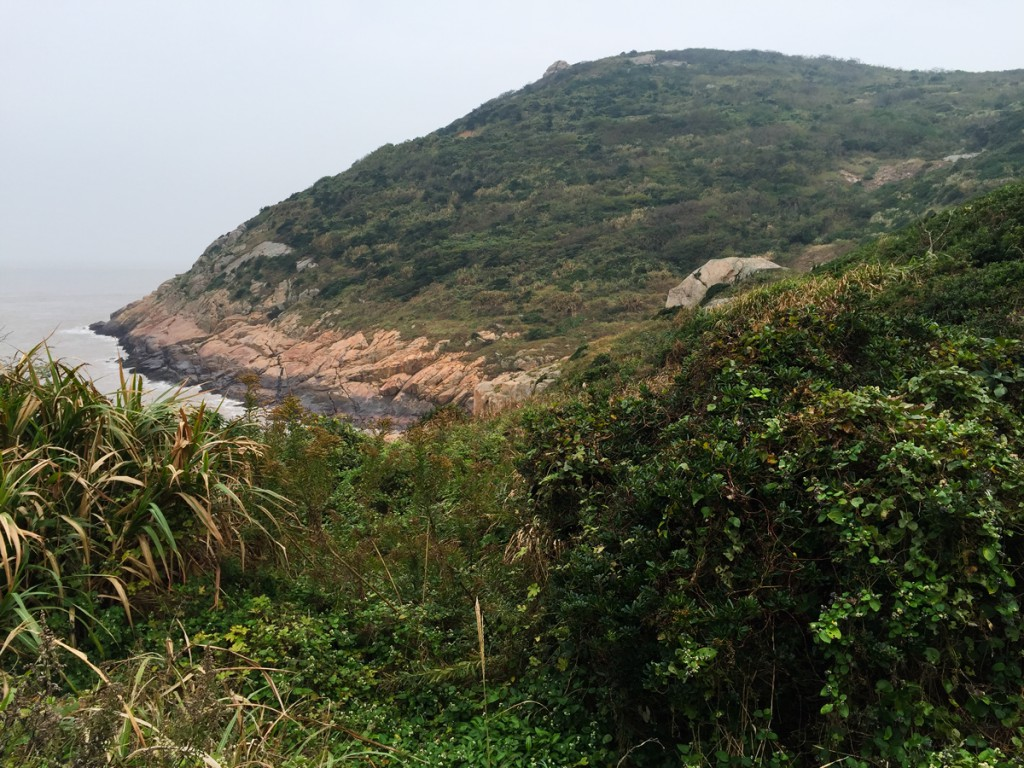 Rock, sea, and hills covered with primary scrub, Sijao Island, 12 Nov. 2015. This scene is from the valley below the main entrance to Liujingtan Scenic Area on the far eastern tip of the island.