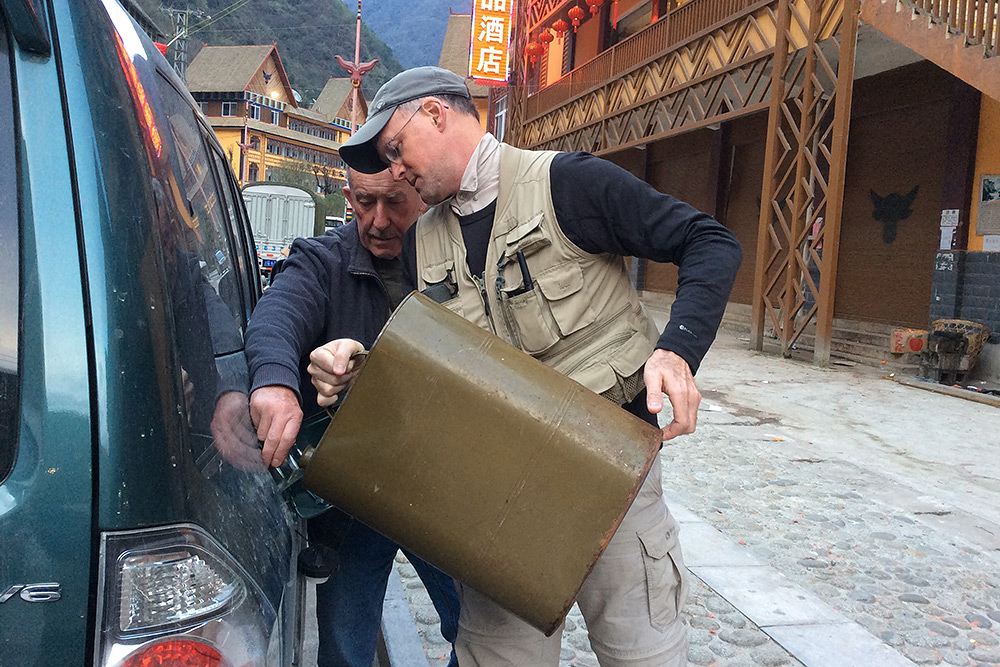 Dulong Gorge has no service stations, and on a long trip it's impossible to carry enough extra fuel over the mountain from Gongshan. It is possible to buy fuel from unofficial local sellers. Here, Brian and I add gasoline purchased from a local fruit merchant. Photo by Elaine Du.