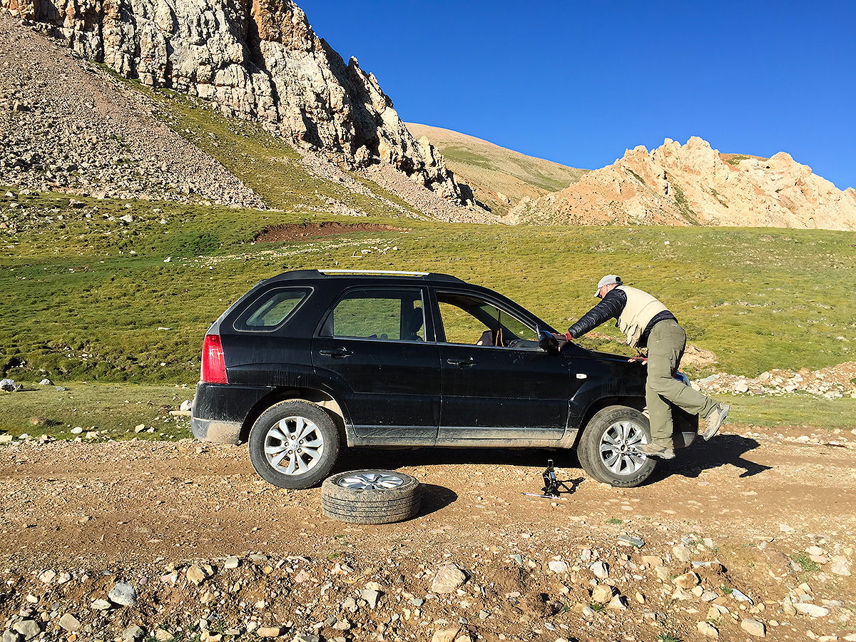Craig Brelsford tightens the spare on Kia Sportage, near Hala Lake, Qinghai. 8 Aug. 2016.