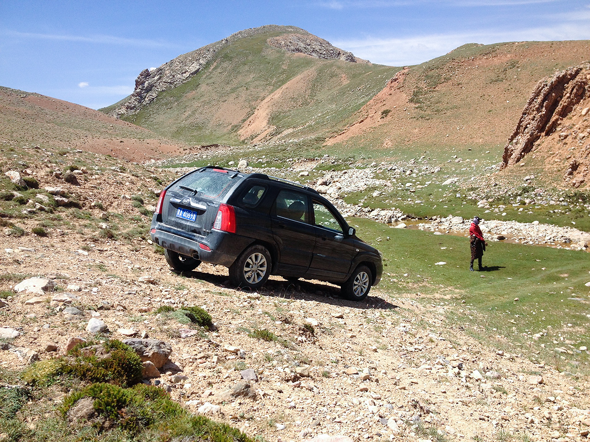 Ren Qing directs Craig (in the Sportage) down a steep path. Near Hala Lake, Qinghai, 9 Aug. 2016.