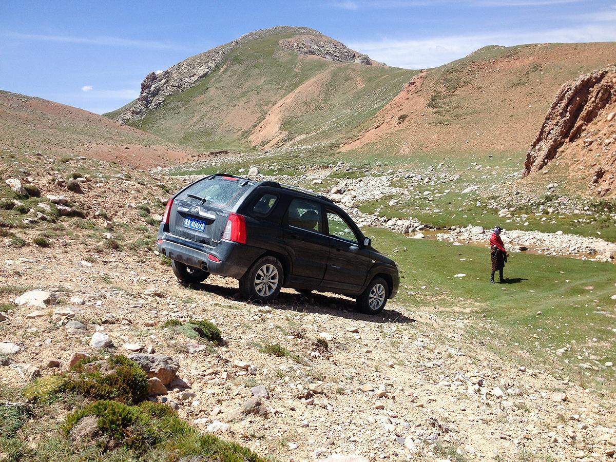 Ren Qing directs Craig (in the Sportage) down a steep path. Near Hala Lake, Qinghai, 9 Aug. 2016.