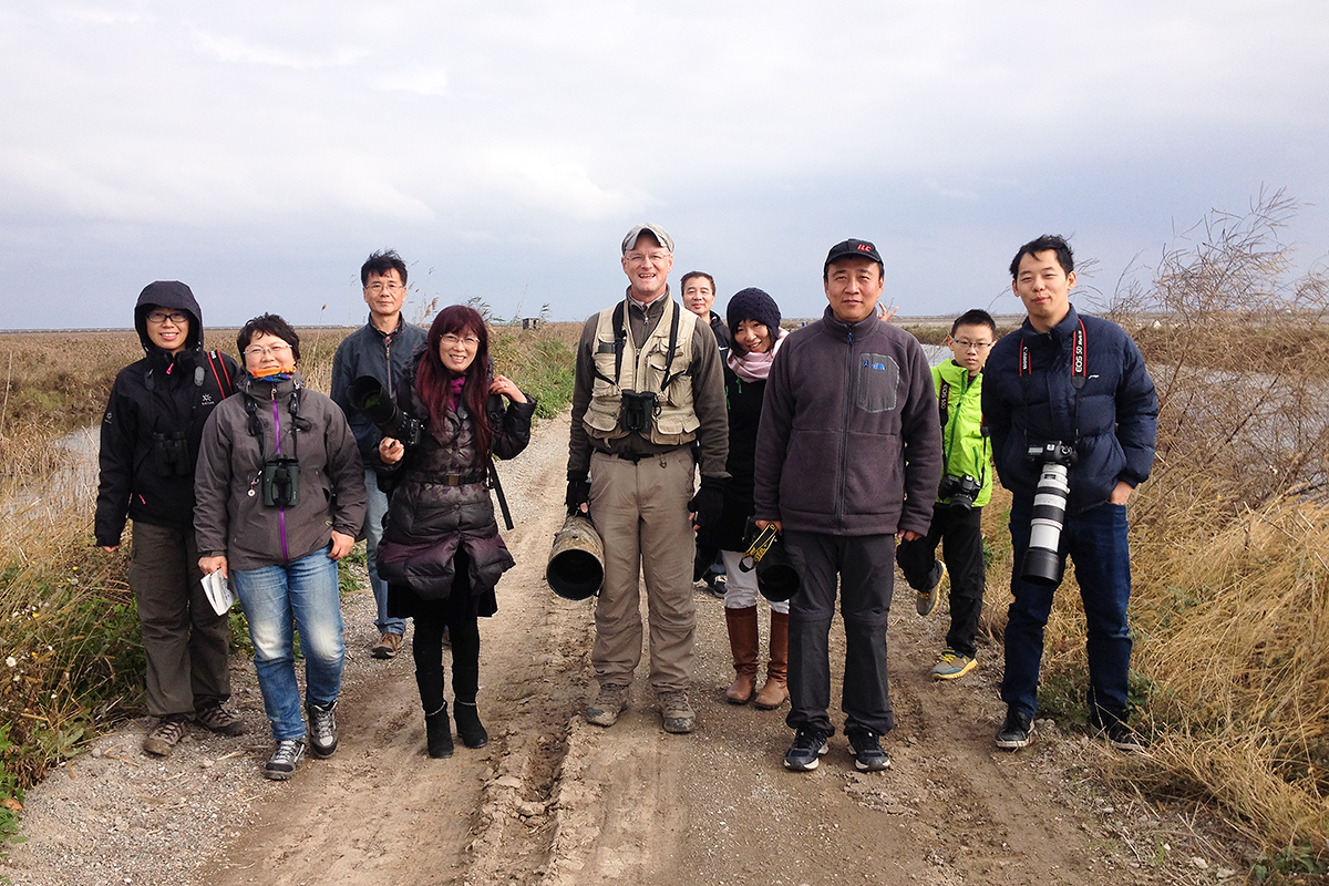 Shanghai birders in defunct wetland reserve, Nanhui, 10 Dec. 2016. As China becomes a middle-income country, Chinese people will find themselves with more and more disposable income and leisure time. This is especially the case in Shanghai, whose living standards are rapidly approaching those of advanced Western countries. Middle-class Chinese will increasingly demand places for rest, relaxation, and nature appreciation. Shanghai currently has such places, and one of them is Cape Nanhui. The tip of the Shanghai Peninsula already has beautiful reed beds and amazing migratory birds, the inheritance of natural Shanghai. With proper management, Shanghai could preserve and showcase those wonders, giving future generations of Shanghainese a gift that will never stop giving. L-R: Zhāng Huá (张华), Zhāng Xuěhán (张雪寒), Lán Bāngxiàn (蓝邦宪), Lán Xī (兰溪), Craig Brelsford, Cài Jiàndōng (蔡见东), Zhāng Xiǎoyàn (张小艳), Hǎo Zhàokuān (郝兆宽), Chéng Yīxuān (程一轩), Xú Yáng (徐扬). Photo by Elaine Du.