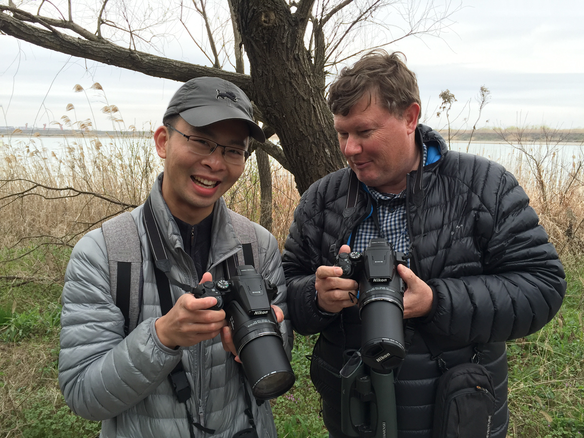 Shanghai Birder KaneXu (L), and Michael Grunwell share a laugh after discovering that they both own the same model of camera, the Nikon Coolpix P900S.