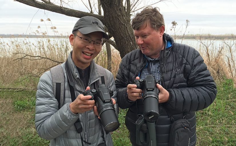 Shanghai Birder KaneXu (L), and Michael Grunwell share a laugh after discovering that they both own the same model of camera, the Nikon Coolpix P900S. (Craig Brelsford)