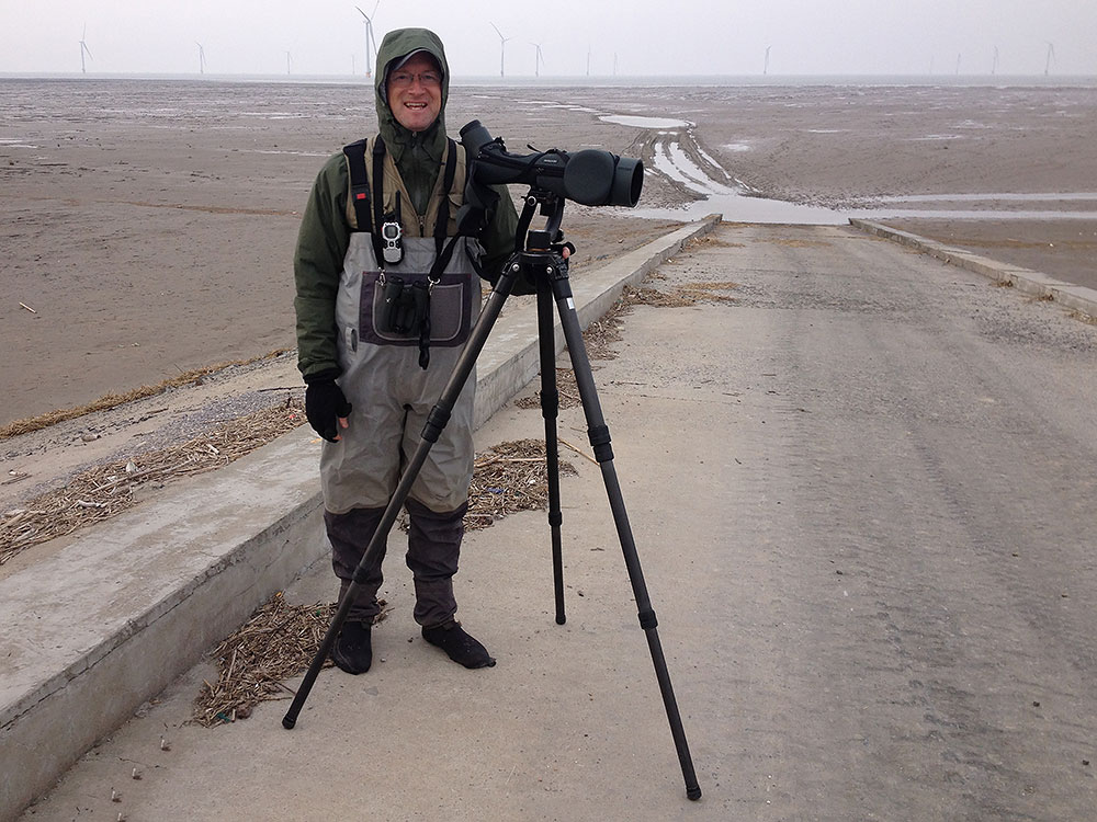Craig Brelsford properly dressed and ready for a scan on the mudflats at Yangkou, 11 April 2015. The mud is normally easy to walk on, but be careful of puddles the bottom of which you cannot see, beware of the mud at the base of the sea wall which is like quicksand, beware of the tide that can sneak up on you, beware of the wind that can sap the heat right out of you, and beware of the silt, fine as dust, which can enter the tiniest joints in your equipment and which when dry hardens like cement. Photo by Elaine Du.