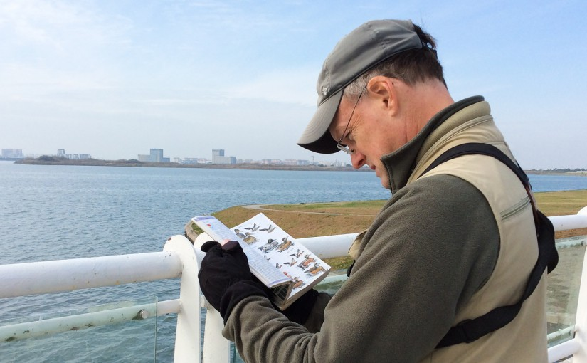 Craig Brelsford consulting Birds of East Asia at Dishui Lake, Shanghai, 28 Nov. 2015. Photo by Elaine Du.
