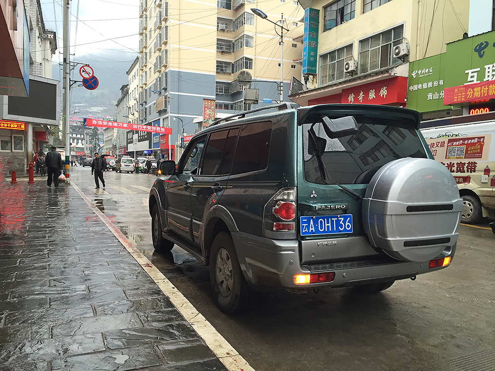 Our rented Mitsubishi Pajero near grocery store in Gongshan, Yunnan, 17 Feb. 2016. We rented this brand-new vehicle at Kunming Changshui International Airport through the rental-car company Héxié Zūchē (和谐租车). It was the perfect car for our trip.